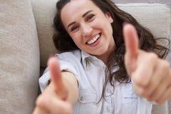 Brunetta meravigliosa che mostra pollice su e che si trova sul sofà Fotografie Stock