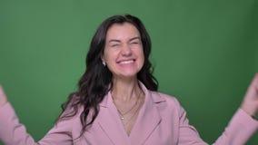Brunettaffärskvinna i det rosa omslaget som visar hennes positiva chock och riktiga lycka in i kamera på grön bakgrund lager videofilmer