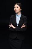 Brunettaffärskvinna i svart dräkt med korsade armar Arkivbilder