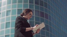Brunettaffärskvinna som aktivt arbetar på minnestavlan stock video