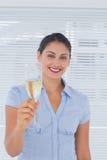 Brunettaffärskvinna som lyfter en flöjt av champagne Fotografering för Bildbyråer
