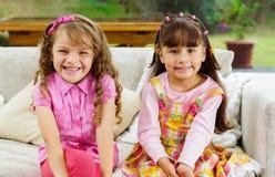 Brunettbarnsystrar som lyckligt sitter på vit Royaltyfria Foton