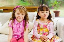 Brunettbarnsystrar som lyckligt sitter på vit Arkivfoto