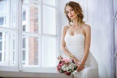 Brunettbrud i den vita bröllopsklänningen för mode med makeup arkivbilder