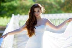 Brunettbrud i den vita bröllopsklänningen för mode med makeup royaltyfri bild