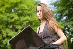 brunettcutie henne bärbar dator Arkivbilder