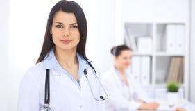 Brunetteärztin auf dem Hintergrund von den Kollegen, die miteinander im Krankenhaus sprechen Arzt ist bereit zu helfen Lizenzfreie Stockfotos