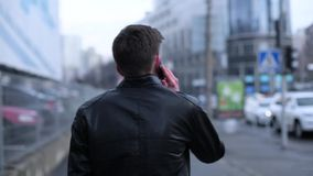 Brunette ατόμων που μιλά σε ένα κύτταρο που περνά από την πόλη απόθεμα βίντεο