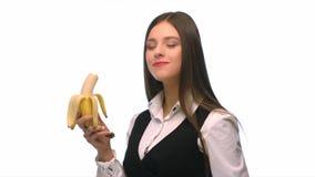Brunette κοριτσιών σε ένα επιχειρησιακό κοστούμι σε ένα άσπρο υπόβαθρο που τρώει μια μπανάνα με τον ήχο απόθεμα βίντεο