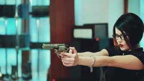 Brunette κοριτσιών στα γυαλιά με τα μαύρα πλαίσια, στόχος σε έναν στόχο που κρατά ένα πυροβόλο όπλο φιλμ μικρού μήκους