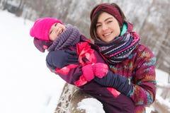 Brunette που αγκαλιάζει την κόρη το χειμώνα στοκ φωτογραφία με δικαίωμα ελεύθερης χρήσης