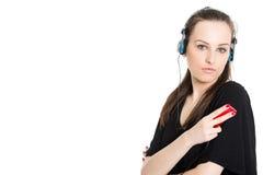 Brunette που ακούει τη μουσική από το φορέα στοκ φωτογραφία