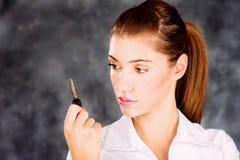 Brunette που εξετάζει ένα κλειδί Στοκ φωτογραφίες με δικαίωμα ελεύθερης χρήσης