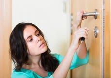 Brunette που εξετάζει τη σπασμένη κλειδαριά της πόρτας στοκ εικόνα με δικαίωμα ελεύθερης χρήσης