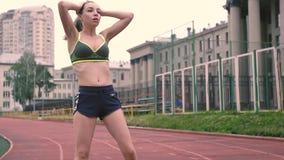 Brunette που κουράζεται αθλητικό του τρεξίματος Έτρεξε σε ένα στάδιο sportswear φιλμ μικρού μήκους