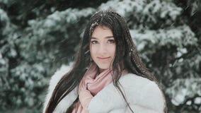 Brunette σε ένα άσπρο παλτό γουνών στα πλαίσια των πράσινων δέντρων έλατου κατά τη διάρκεια μιας χιονοθύελλας φιλμ μικρού μήκους