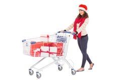 Brunette στο καπέλο santa με το καροτσάκι αγορών Στοκ εικόνα με δικαίωμα ελεύθερης χρήσης