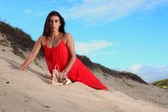 Brunette στο κόκκινο φόρεμα που στηρίζεται στην παραλία στοκ εικόνες
