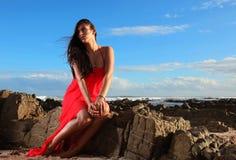 Brunette στο κόκκινο φόρεμα στην παραλία στοκ εικόνα με δικαίωμα ελεύθερης χρήσης