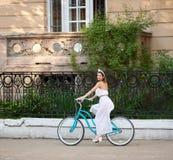 Brunette χαμόγελου στο άσπρο φόρεμα που οδηγά το εκλεκτής ποιότητας μπλε ποδήλατο κάτω από την πράσινη παλαιά οδό στοκ εικόνες