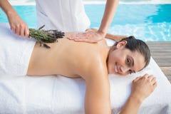 Brunette χαμόγελου που παίρνει ένα aromatherapy poolside επεξεργασίας Στοκ Εικόνες