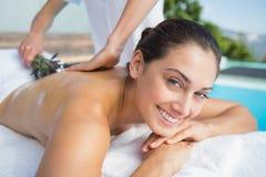 Brunette χαμόγελου που παίρνει ένα aromatherapy poolside επεξεργασίας Στοκ Φωτογραφία