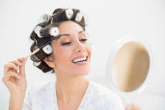 Brunette χαμόγελου στους κυλίνδρους τρίχας που φαίνονται διαθέσιμοι καθρέφτης και brus χεριών Στοκ Εικόνες