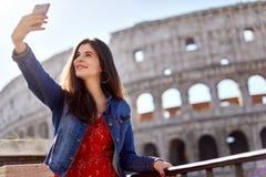 Brunette χρησιμοποιώντας το τηλέφωνο και παίρνοντας selfie στοκ εικόνα