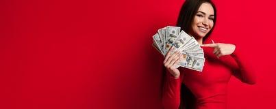 Όμορφη γυναίκα στην κόκκινη δέσμη εκμετάλλευσης φορεμάτων των τραπεζογραμματίων χρημάτων στοκ εικόνες