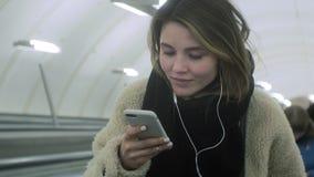 Η νέα γυναίκα brunette χρησιμοποιεί ένα τηλέφωνο με τα ακουστικά απόθεμα βίντεο