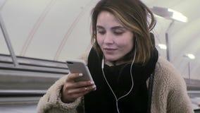 Η νέα γυναίκα brunette χρησιμοποιεί ένα τηλέφωνο με τα ακουστικά φιλμ μικρού μήκους