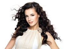 Όμορφη γυναίκα brunette με τη μακριά σγουρή τρίχα ομορφιάς. Στοκ Φωτογραφίες