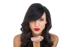 Προκλητικό brunette με τα κόκκινα χείλια που φυσούν το φιλί στη κάμερα Στοκ Φωτογραφία