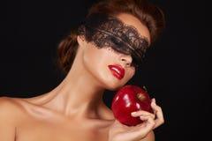Η όμορφη προκλητική γυναίκα brunette με τη δαντέλλα που τρώει τα κόκκινα υγιή τρόφιμα μήλων, νόστιμα τρόφιμα, οργανική διατροφή,  Στοκ Εικόνες