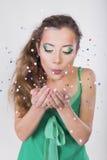 Η γυναίκα Brunette φυσά μακριά το κομφετί στη γιορτή γενεθλίων της Στοκ Εικόνα