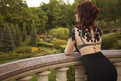 Όμορφη προκλητική πλούσια γυναίκα πολυτέλειας brunette που στέκεται σε ένα μπαλκόνι Στοκ φωτογραφίες με δικαίωμα ελεύθερης χρήσης