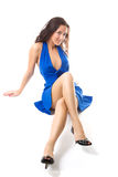 Brunette. Portrait of beautiful brunet is sitting on floor in blue dress Stock Image
