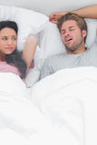 Brunette annoyed by the snoring of her husband. Next to her Royalty Free Stock Photography