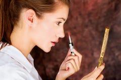 Brunette applying lipstick. Pretty young brunette applying lipstick while looking at the mirror Stock Photo
