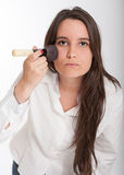 Brunette applying make-up Royalty Free Stock Image