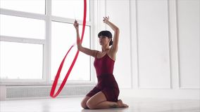 Brunette artistic gymnast is sitting on a floor in a class and waving red ribbon stock footage