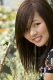 Brunette asian girl. With green pine Royalty Free Stock Photography