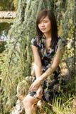 Brunette asian girl. Sitting at the lakeside Stock Images