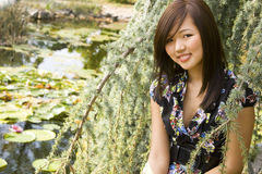 Brunette asian girl. Sitting at the lakeside Royalty Free Stock Image