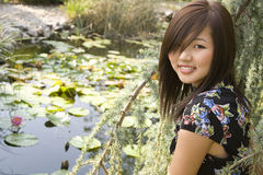 Brunette asian girl sitting at the lakeside. There are waterlillies on the surface of the water Royalty Free Stock Photos