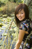 Brunette asian girl sitting at the lakeside. There are waterlillies on the surface of the water Royalty Free Stock Images