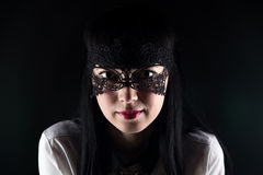 Brunette asian woman and lace mask. On black background royalty free stock photo