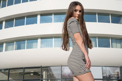 Brunette Asian woman wearing striped dress standing in front of the white building in the city Royalty Free Stock Images