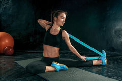 The brunette athletic woman exercising with rubber tape. On black wooden floor Royalty Free Stock Photos