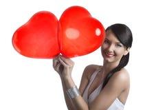 Brunette atractivo con sonrisas en forma de corazón de los globos Fotografía de archivo libre de regalías